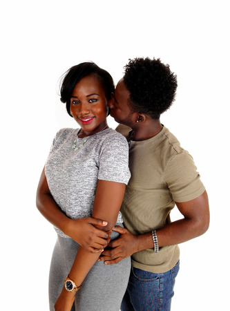 romantic couple: A pretty African American couple standing isolated for white background, the man is kissing his girlfriend. Stock Photo