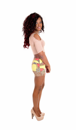 short skirt: A pretty African American woman in a short skirt a t-shirt and heels, standing in profile isolated for white background.