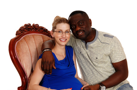 A happy African American man with his Caucasian wife sitting in a pink armchair, she is pregnant, isolated for white background.