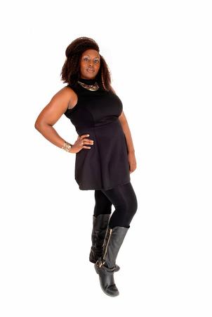 cuerpo completo: Una foto de cuerpo entero de una mujer afroamericana con botas y un vestido negro de pie aislado en fondo blanco. Foto de archivo