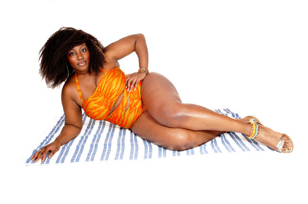 A young African American woman lying on a towel on the floor in a orange bikini, isolated for white background. photo