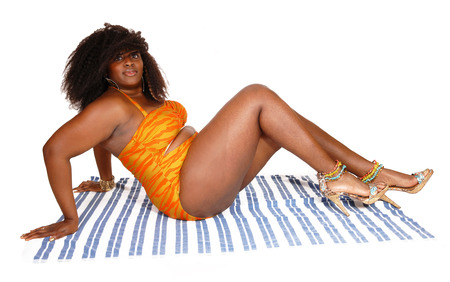 A young big African American woman in a orange bikini sitting on a towel on the floor, isolated for white background. photo