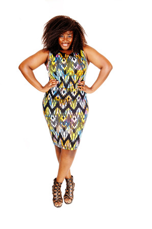 A lovely smiling African American woman standing in a colourful dress isolated foe white background. Stock Photo