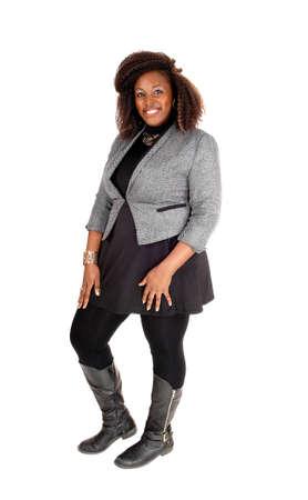 completo: Una foto de cuerpo entero de una joven mujer afroamericana en un vestido negro y chaqueta y botas de color gris, de pie aislado en fondo blanco.