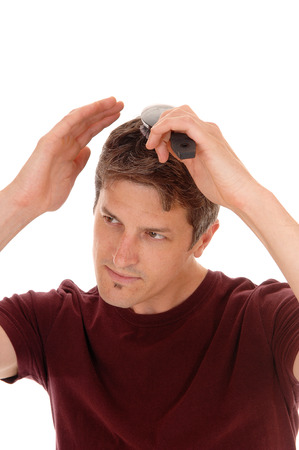hair treatment: A handsome young man in a burgundy shirt brushing his hair, isolated for white background.