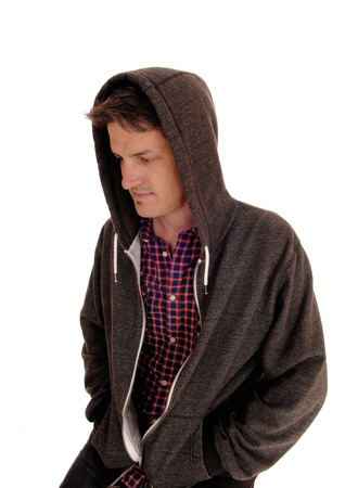 hoody: A handsome young man sitting with a hoody over his head looking down, isolated for white background. Stock Photo