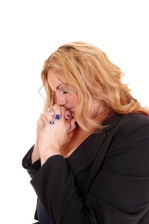 A blond young plus size women in profile with her hands folded, praying,