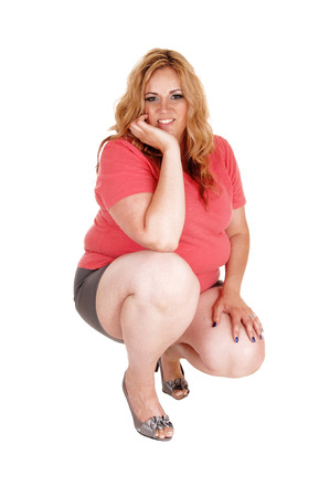 A plus size pretty woman in shorts crouching in the floor, holding her head in one hand, isolated for white background. Stock Photo