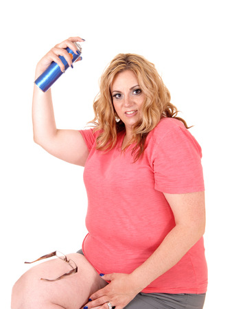 hairspray: A lovely plus size woman sitting in shorts on a chair and spraying hair spray on her hair, isolated foe white background. Stock Photo