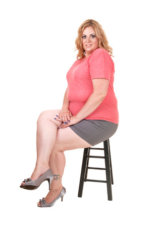 A blond plus size woman sitting in shorts and a pink sweater on a chair,