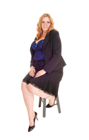 A young blond plus size woman in a black skirt and jacket and corset,  