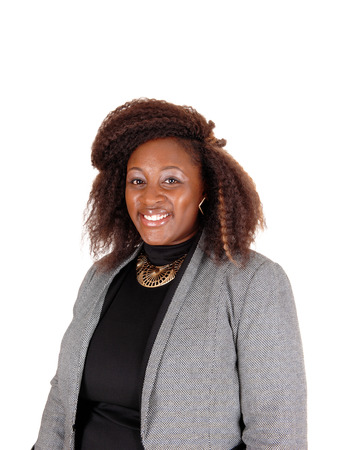 A lovely portrait picture of a African American woman, smiling in a grey jacket and black dress, isolated for white background.