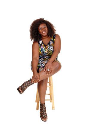 piernas con tacones: Un sonriente mujer encantadora afroamericano sentado en un colorido vestido en una silla, aislado de fondo blanco. Foto de archivo