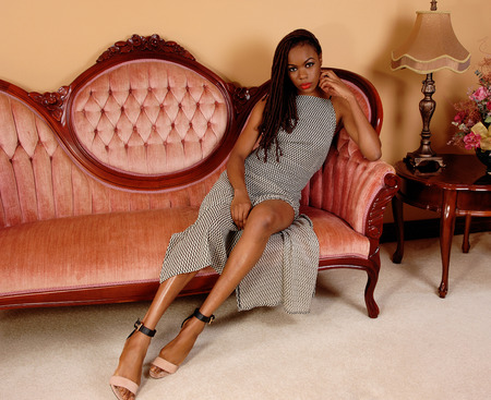 baited: A beautiful young African American woman in a gray dress sitting on a pink antic sofa in the living room.