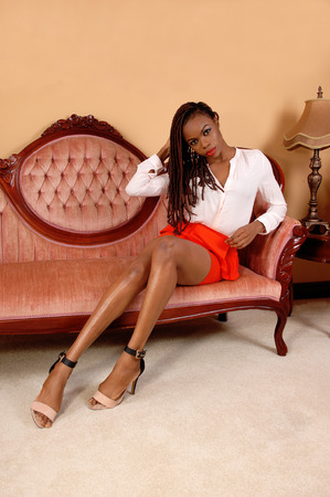 baited: A beautiful young African American woman in a red skirt sitting on a pink antic sofa in the living room.