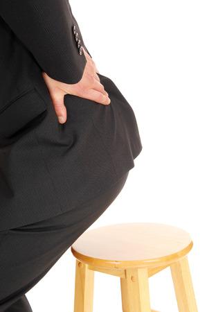 levantandose: Un hombre de negocios de levantarse de la silla sosteniendo su mano en la espalda para el dolor de la artritis, parte del cuerpo, aislado de fondo blanco.