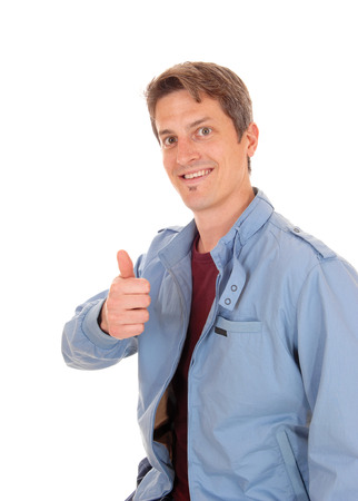 thump: A young happy man in a blue jacket standing for white background with his thump up and smiling. Stock Photo