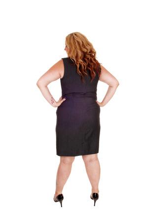 Een volledige lengte beeld van een plus size vrouw in een grijze jurk staan van de rug, geïsoleerde voor witte achtergrond.