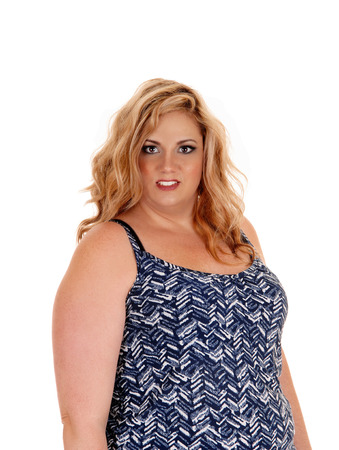 plus sized: A beautiful plus sized young woman in a blue and white dress standing isolated for white background.