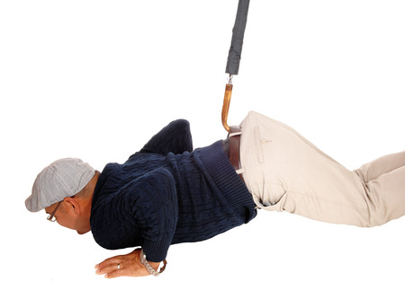 fainted: A Hispanic man with a had lying on the floor and gets pulled up with an umbrella, isolated for white background.