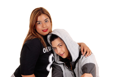 foe: A closeup picture of a Caucasian and a East Indian woman, one in a hoody hugging, isolated foe white background. Stock Photo