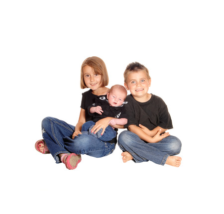 whitebackground: A young girl and her brother sitting on the floor isolated for white background, holding there three weeks old baby.