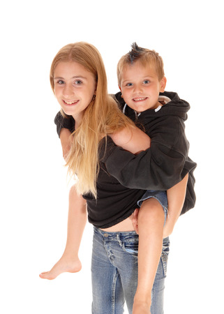 A closeup picture of a young girl caring her little brother on her back, smiling, isolated for white background. Stock Photo