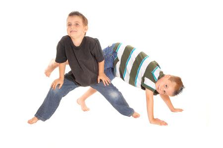 Due piccoli anno ragazzi Fife, piedi nudi e in jeans, ballare sul pavimento, isolato per sfondo bianco.