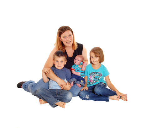 three generations of women: A mother with her boy and girl sitting on the floor holding her newborn baby in her arms, isolated for white background. Stock Photo