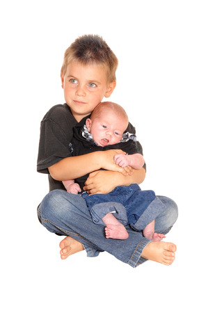 weeks: A little boy sitting on the floor and holding his new three weeks old brother in his lap, isolated for white background. Stock Photo