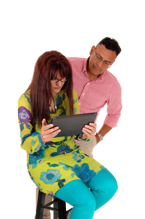 interested: A Caucasian woman with her Hispanic man looking interested on there tablet computer, isolated for white background. Stock Photo