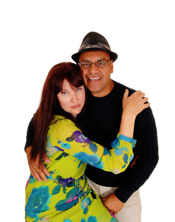 hi hat: A Caucasian woman hugging her Hispanic husband, hi is smiling and wearing a hat, isolated for white background.