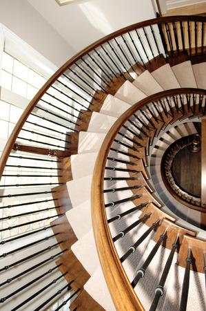 #44376464   Eine Schöne Runde Treppe In Einem Nahaufnahmebild über Drei  Fußböden Im Eichenholz Mit Teppich Und Einem Fenster Auf Dem Links.