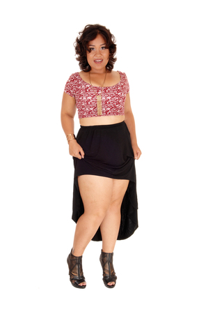 mixed raced: A mixed raced young woman standing isolated for white background in a black skirt, showing her legs. Stock Photo