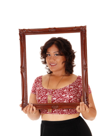 mixed raced: A beautiful young mixed raced woman holding an picture frame in front of her, isolated for white background.