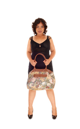 mixed raced: A young mixed raced woman standing in a black dress from the frond, holding her handbag, isolated for white background. Stock Photo