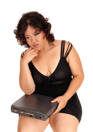 mixed raced: A pretty but sad mixed raced woman sitting in a black dress, holding her broken laptop, isolated for white background.