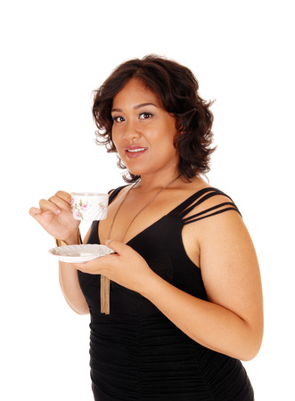 mixed raced: A lovely young mixed raced woman in a black dress holding a saucer and drinking coffee, in a black dress, isolated for white background. Stock Photo