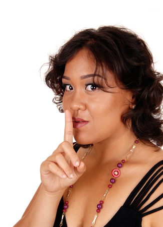 mixed raced: A mixed raced woman, looking into the camera holding her finger over her mouth gesturing silence, isolated for white background. Stock Photo