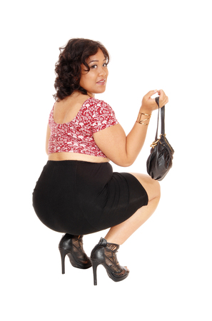 mixed raced: A young mixed raced woman in heels and black skirt crouching on the floor holding her purse, isolated for white background.