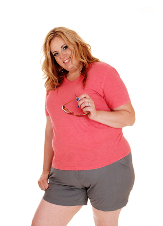 A Blond Plus Size Woman Standing In Shorts And A Pink Sweater