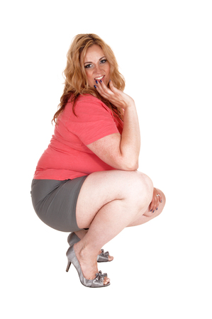 A lovely young plus size woman crouching on the floor, in gray shorts and high heels, isolated for white background..