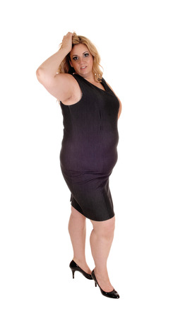 Plus size young woman standing isolated for white background with her hand on her head, in high heels.