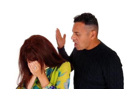 problemas familiares: Un hombre hispano gritando a su mujer de raza caucásica levantar su mano, la violencia doméstica, aislado de fondo blanco.