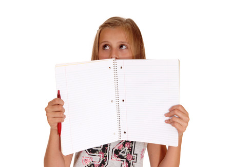 A schoolgirl holding her blank folder for her face, looking scared,isolated for white background. Archivio Fotografico