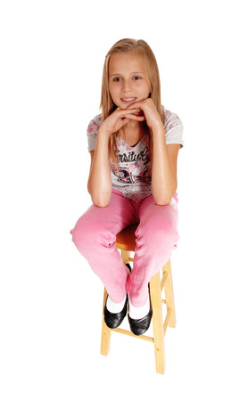 chin on hands: A blond young girl sitting on a chair with her hands under her chin isolated for white background