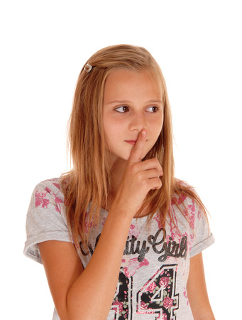 A lovely blond young girl standing for white background holding her
