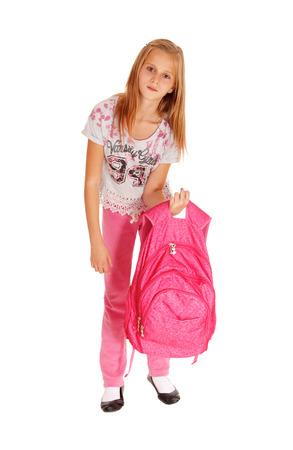 A blond pretty girl lifting her heavy pink backpack for school, standing isolated for white background. Banco de Imagens