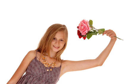 girl in burgundy dress: A pretty young girl in a burgundy dress holding up two roses, smiling, isolated for white background.