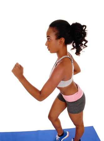 athletic wear: A slim young african american woman running in sports wear with her long black hair, on a blue mat, isolated for white background.